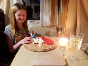 Klara fixade tomat- och mozzarellasallad till pastan.
